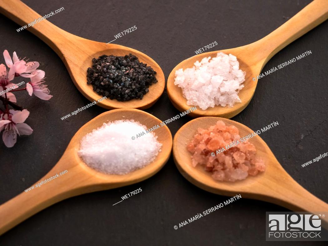 Stock Photo: Wooden spoons with himalayan salt, black hawaii salt, common salt and salt flakes on a slate plate.