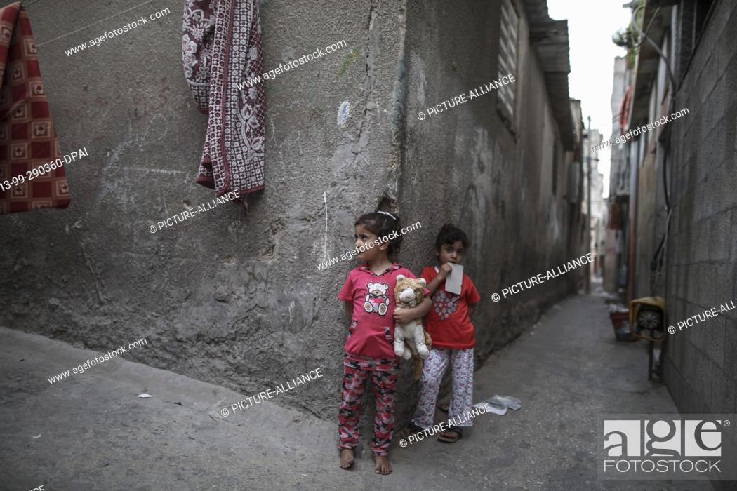 dpatop - Two Palestinian refugee girls play outside the