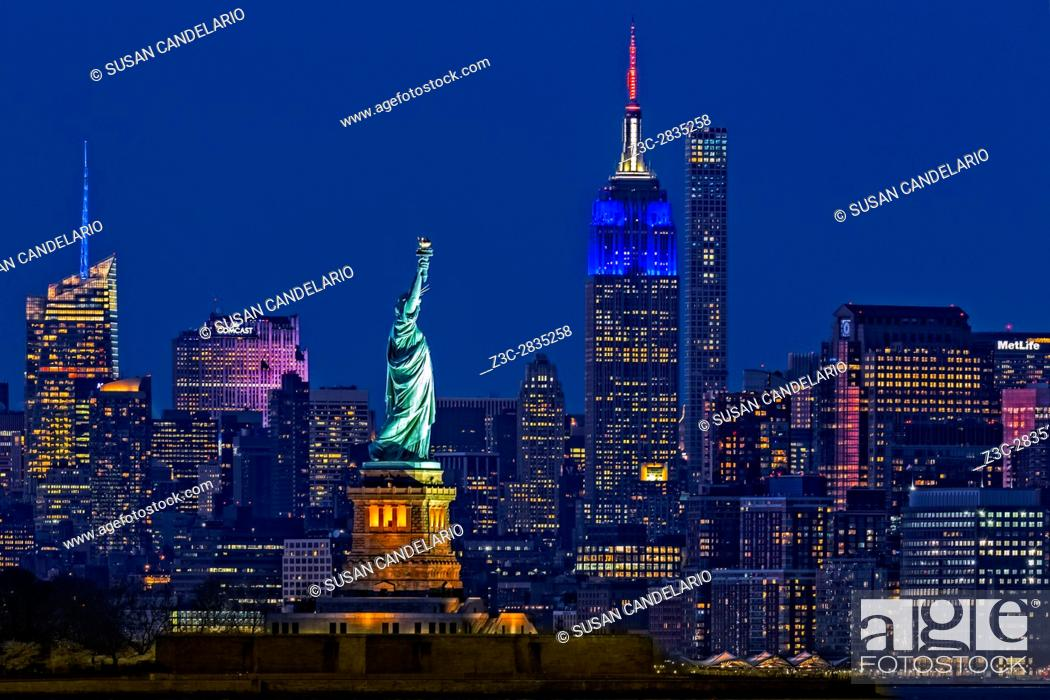 Stock Photo: Empire State And Statue Of Liberty II - The illuminated midtown Manhattan skyline with the Empire State Building (ESB) lit up.