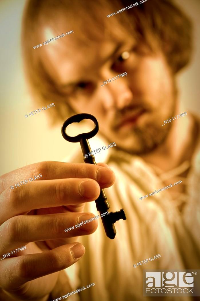 Stock Photo: Young man holding a key.