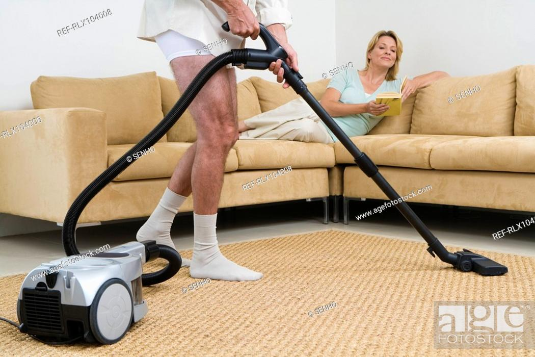 Stock Photo: Senior couple, man vacuuming at home, woman lying on sofa.