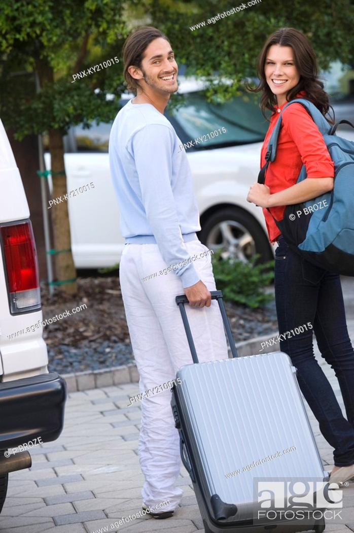 Stock Photo: Couple holding luggage and smiling.