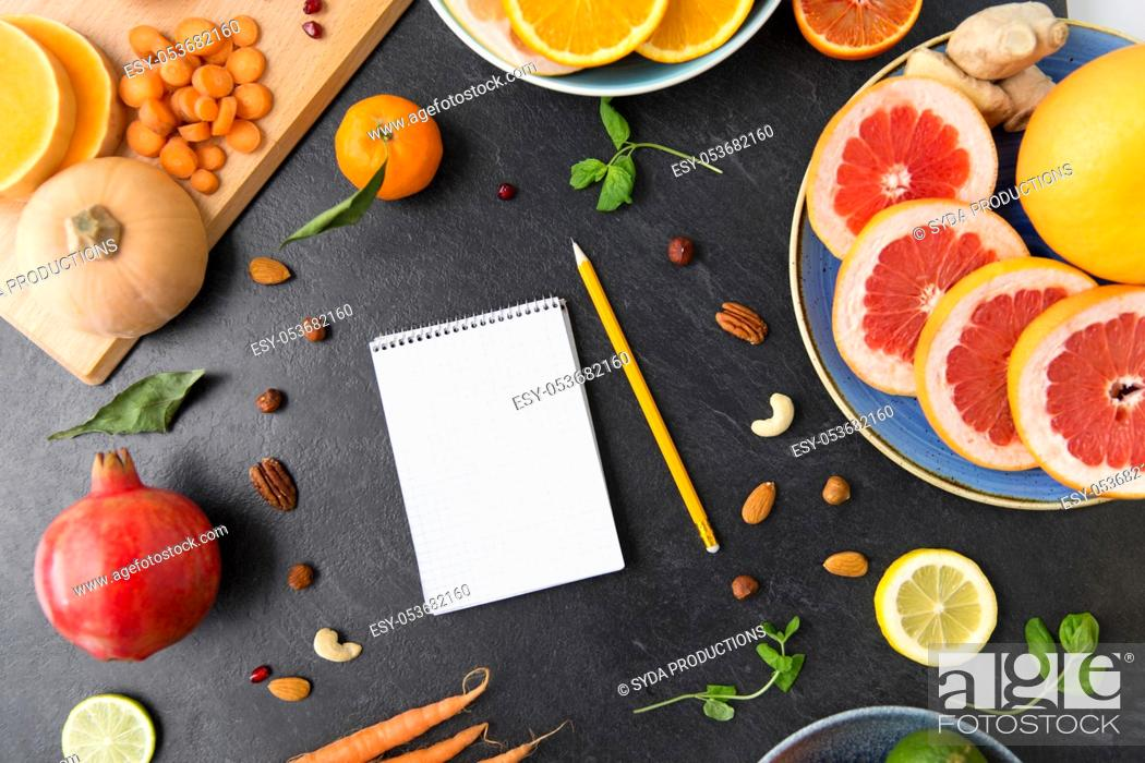 Stock Photo: close up of notebook, fruits and vegetables.