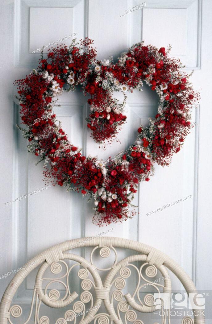 Stock Photo: Flower heart wreath on door.