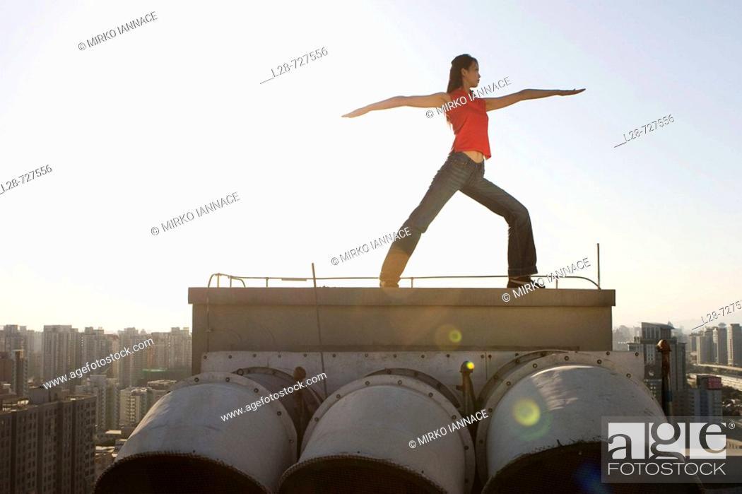 Stock Photo: Woman doing yoga on roof.