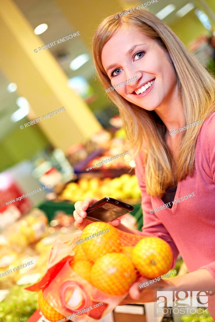 Stock Photo: Germany, Cologne, Young woman with smart phone and oranges in supermarket, smiling.