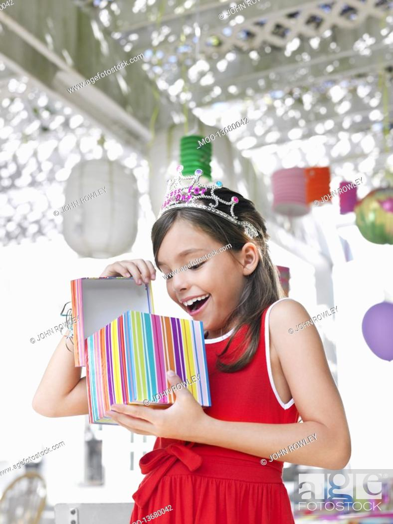 Stock Photo: Young girl 7-9 opening birthday present at party.