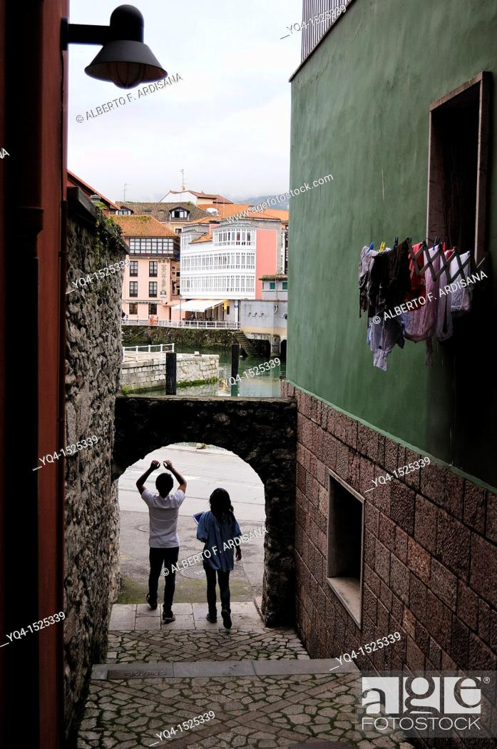 Stock Photo: Young couple walking through one of the alleys that accesses the port of Llanes, Asturias. Spain.