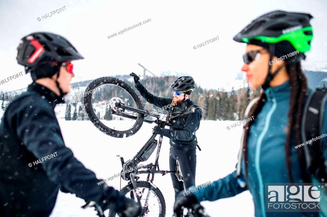 Stock Photo: A group of young mountain bikers standing on road outdoors in winter.