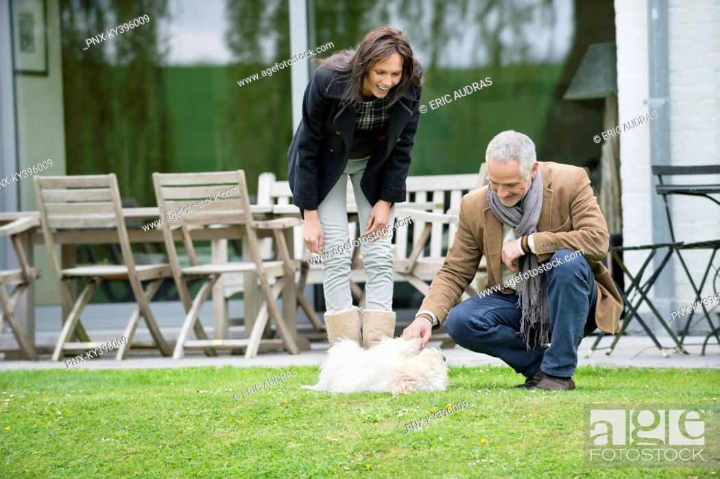Stock Photo: Couple playing with their pets in a garden.