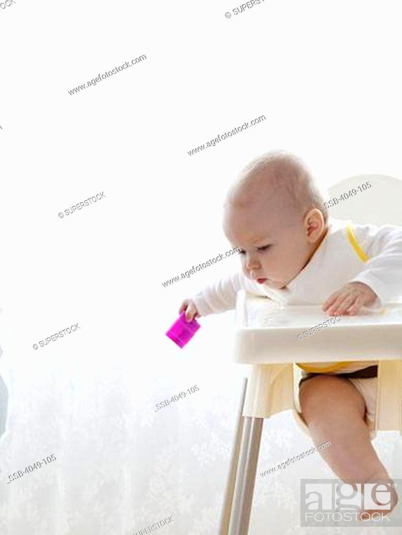 Newborn Baby Sitting In High Chair Looking At The Ground Stock