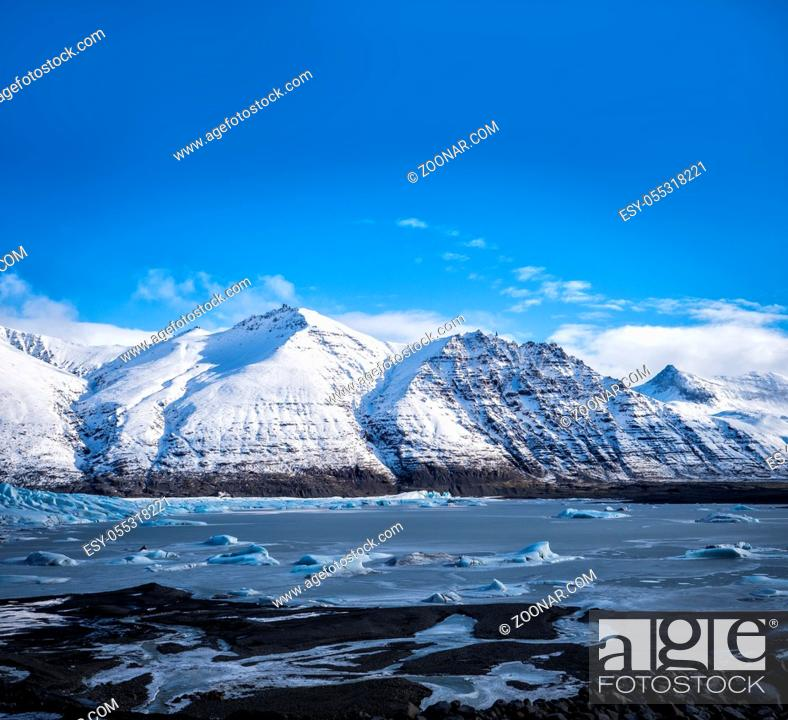 Photo de stock: Huge majestic glacier's icy surface by snowy mountain in Iceland.