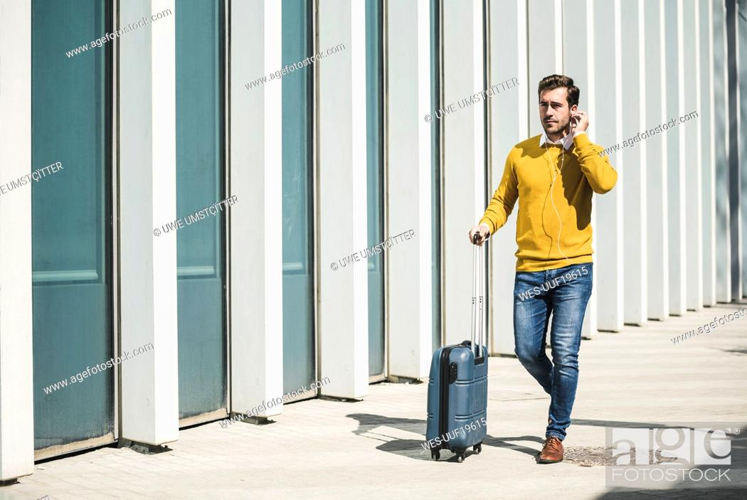Stock Photo: Young man with rolling suitcase and earphones in the city on the go.