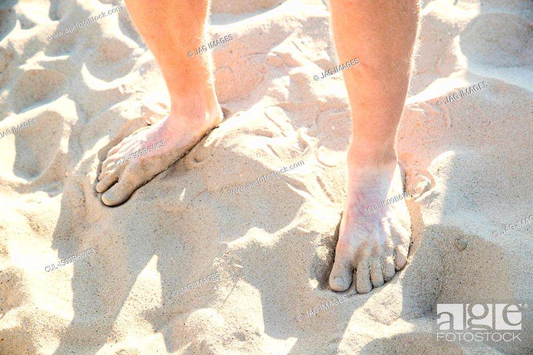 Stock Photo: Bare feet and ankles of young man standing on dry sandy beach.