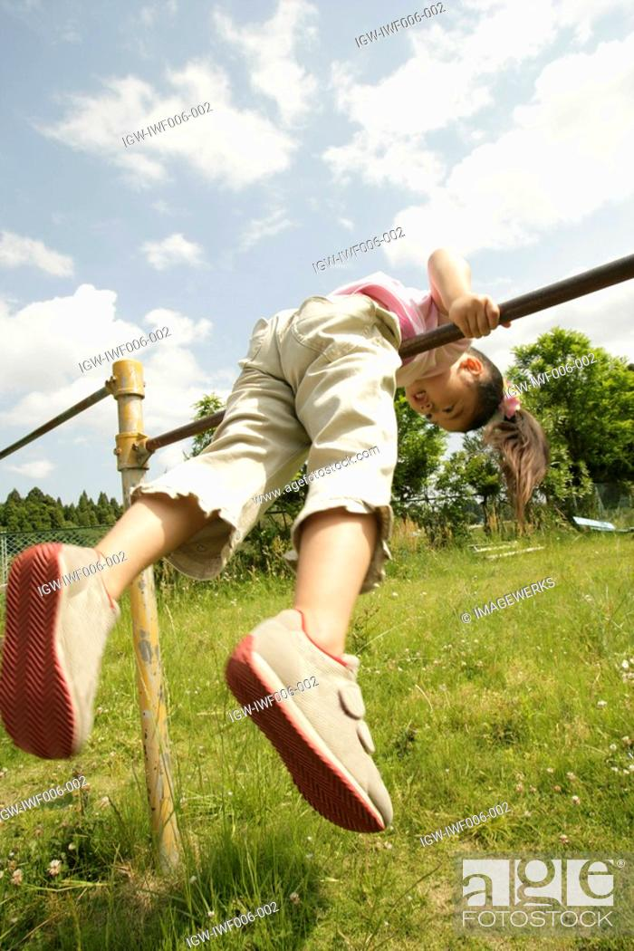 Stock Photo: A young girl balancing herself on the rod.