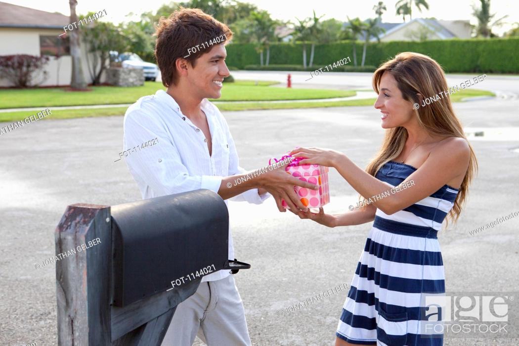 Stock Photo: A young couple standing by mailbox, playfully fighting over a gift.