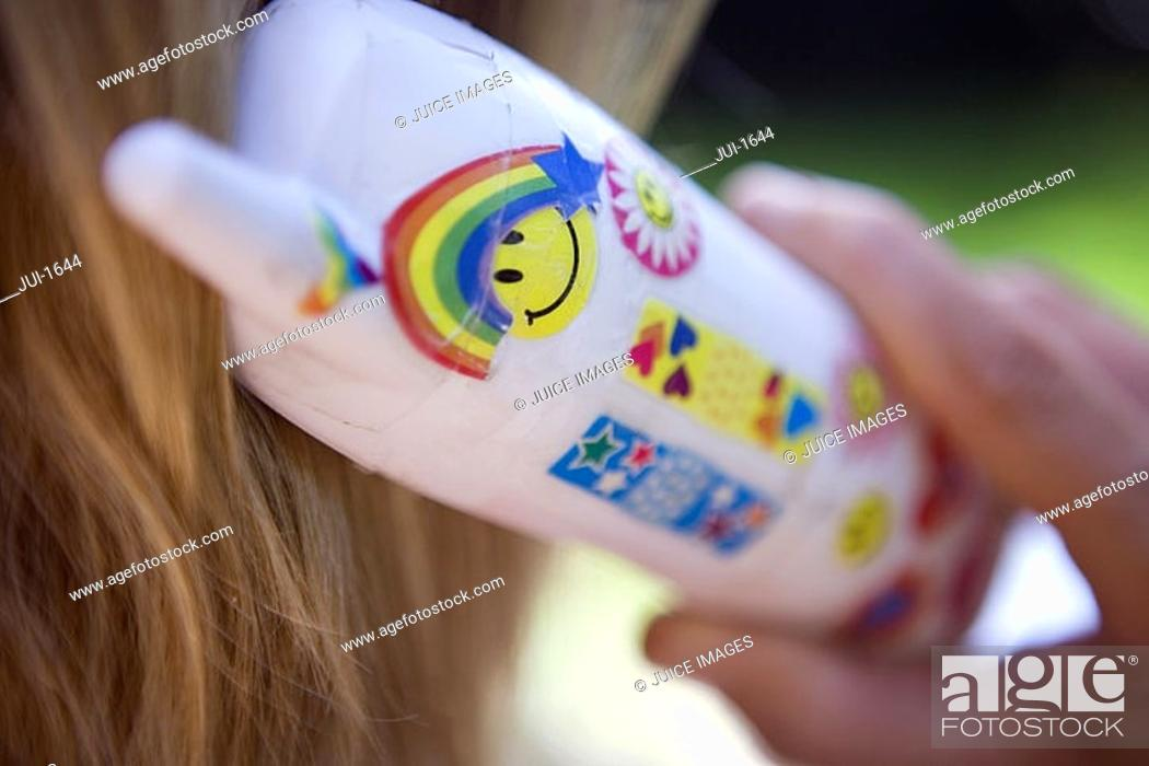 Stock Photo: Woman using white mobile phone decorated with smiley face, rainbow and heart shape symbols, close-up, rear view, focus on foreground.