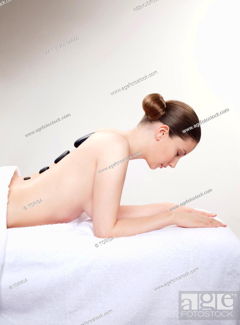 Stock Photo: Woman having a hot stones treatment, eyes closed.