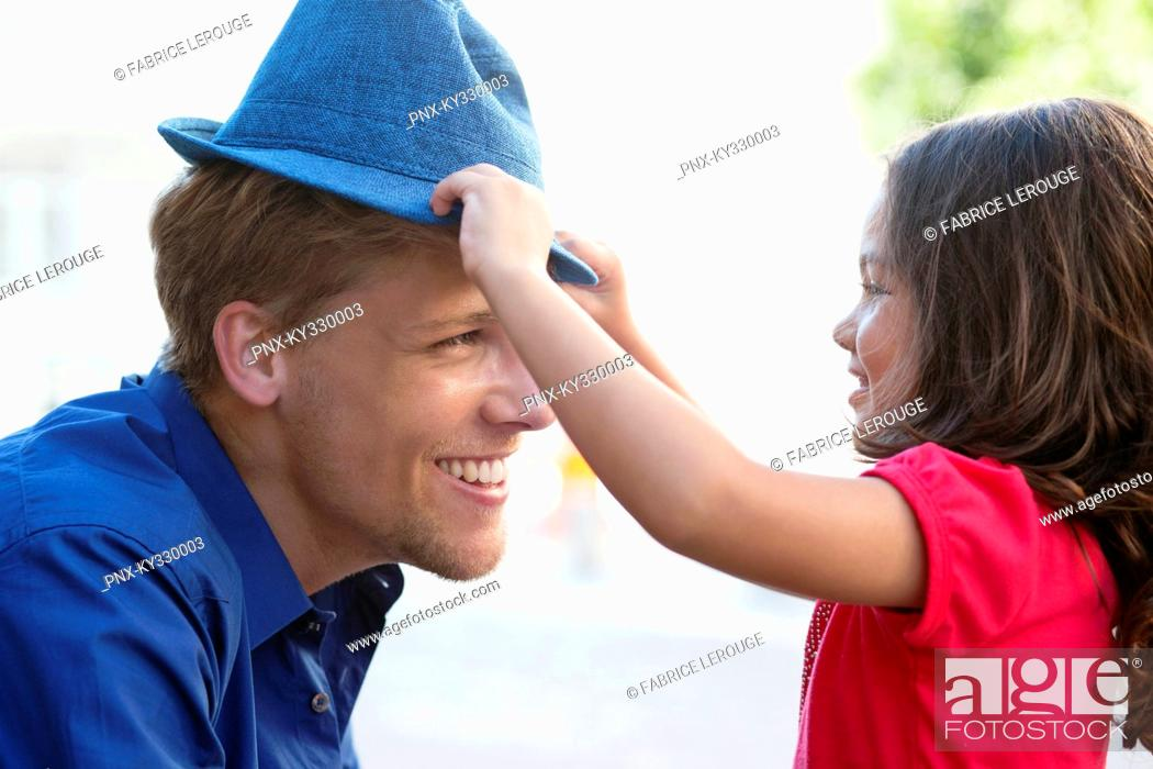 Stock Photo: Cute little girl putting on a hat to her father.