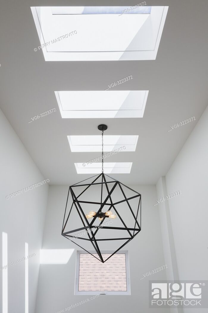 Stock Photo: Skylight windows and black steel hexagonal lighting fixture with five clear glass bulbs hung above the staircase inside a modern cube style home.