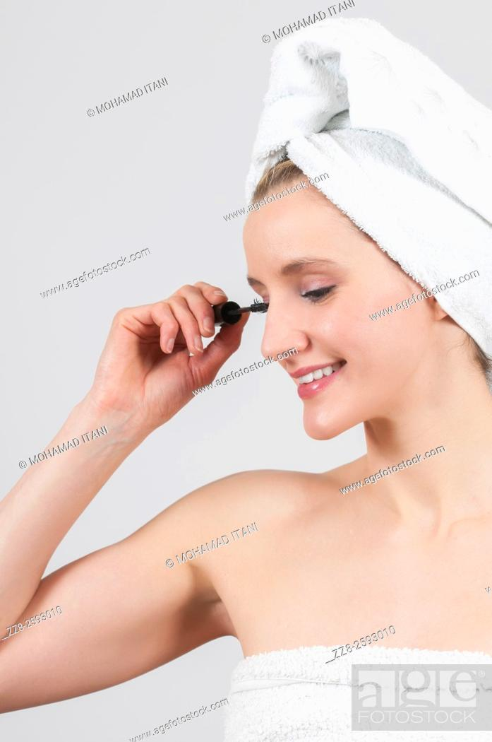 Stock Photo: Woman applying mascara after shower with white towel on her head.