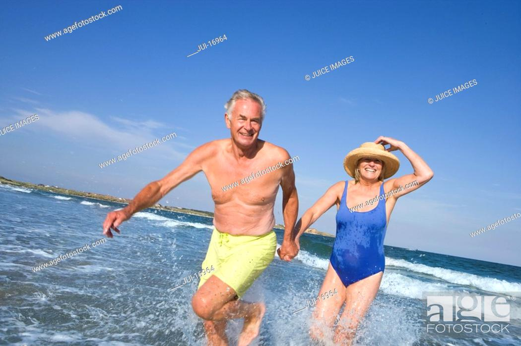 Stock Photo: Senior couple walking in sea.