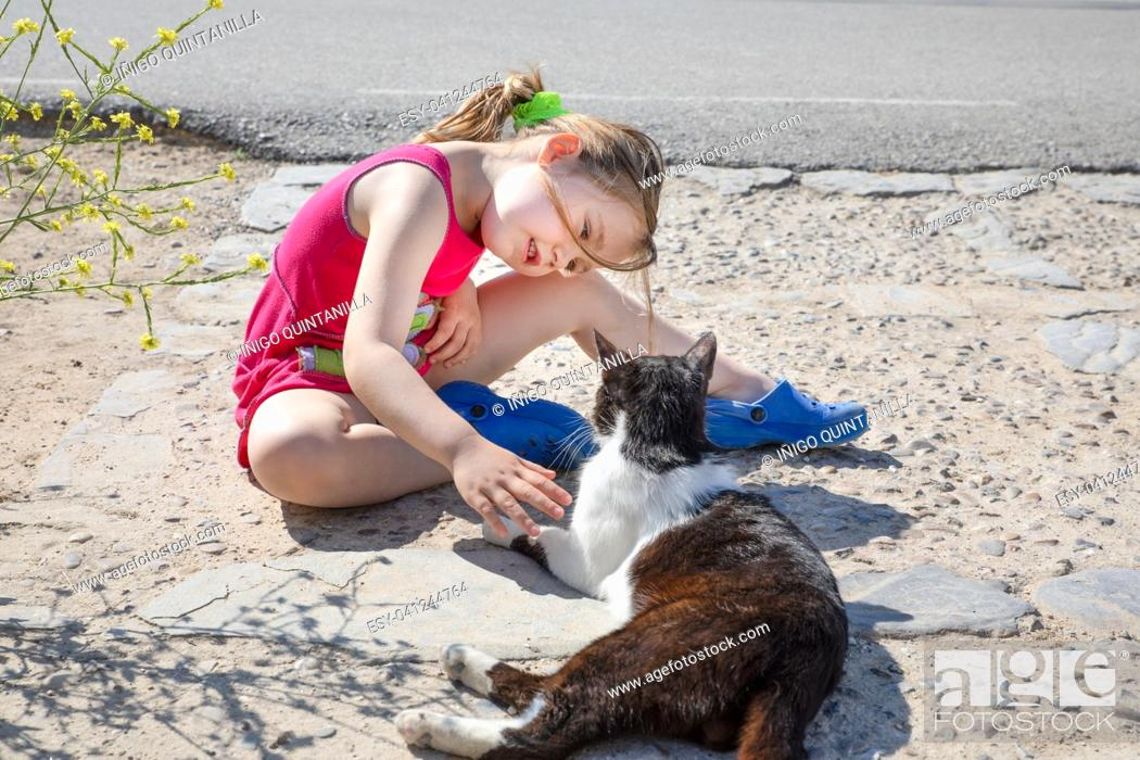 Stock Photo: little girl, five years old child sitting on the ground, smiling and looking at white and black cat, on the street in Summertime.