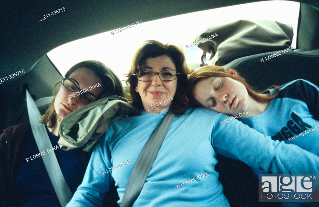 Stock Photo: Mother with daughters traveling in back of car.