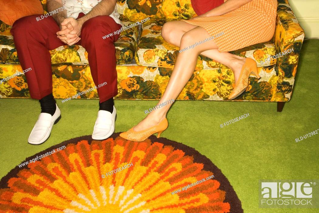 Stock Photo: Female legs playing footsie with male legs by colorful retro sofa.