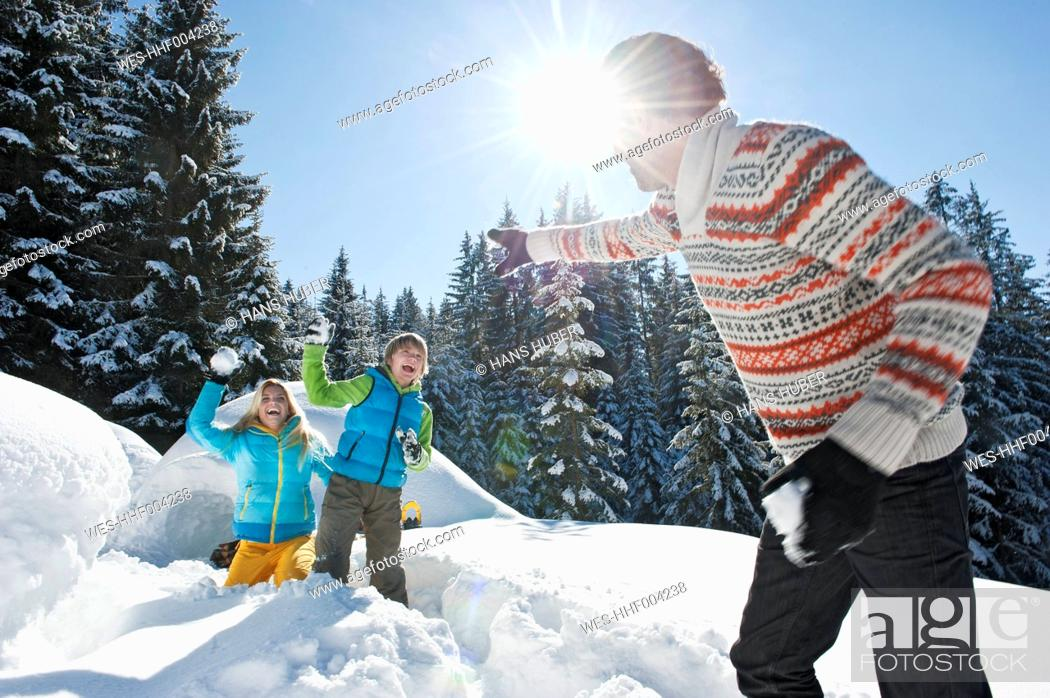 Stock Photo: Austria, Salzburg County, Family playing near igloo.