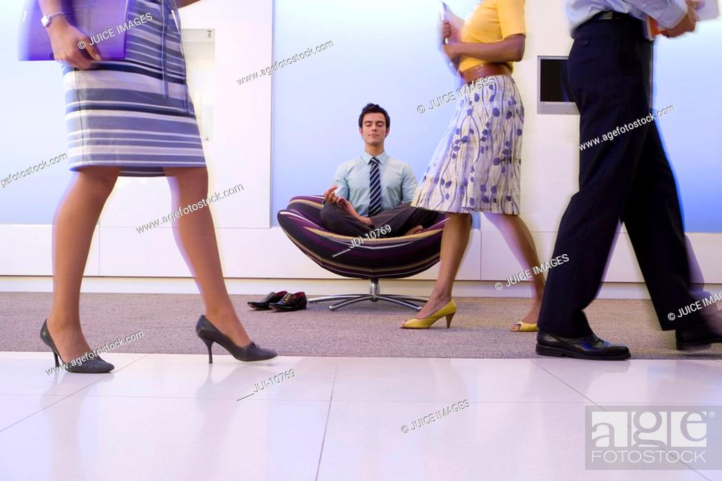 Stock Photo: Businessman meditating in chair in office foyer, colleagues walking past, low section blurred motion.