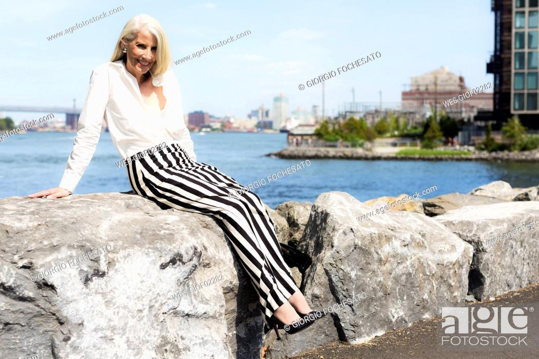 Stock Photo: USA, Brooklyn, smiling mature woman sitting on a wall.