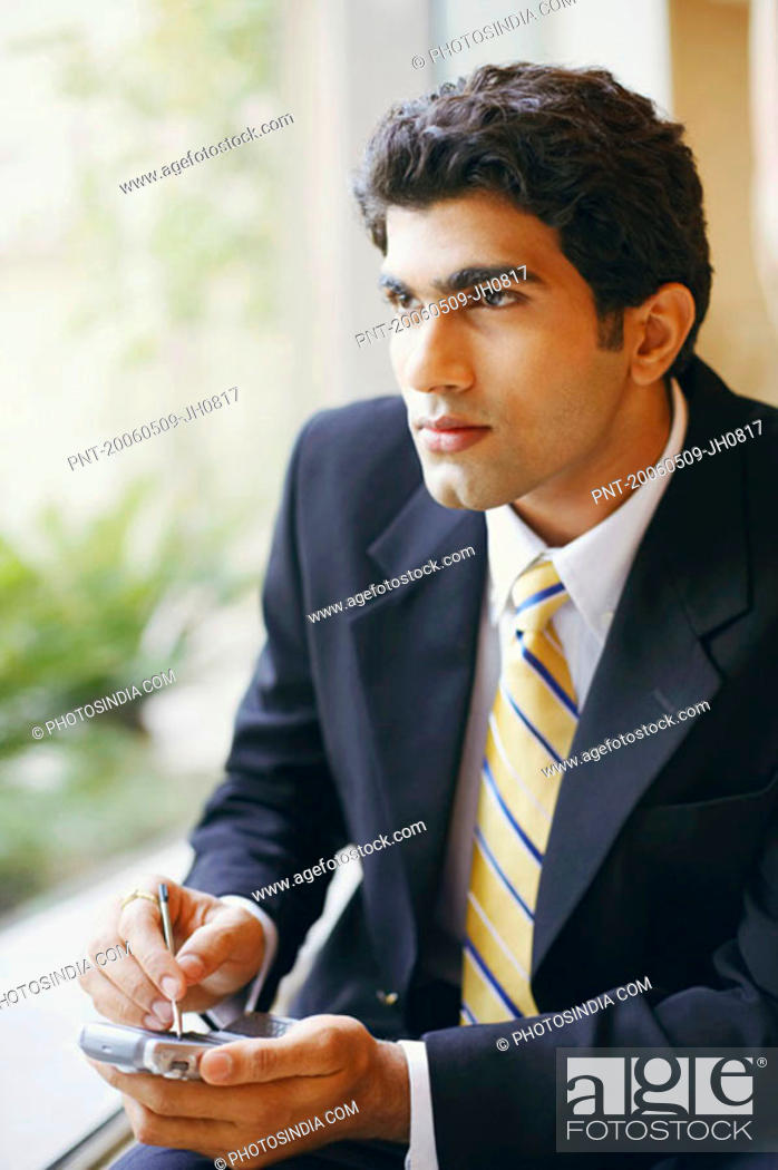 Stock Photo: Close-up of a businessman using a personal data assistant.