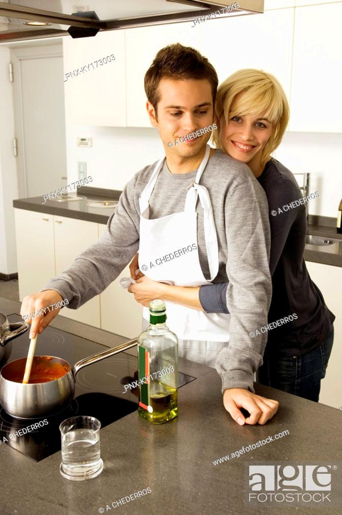 Stock Photo: Young man cooking food and a young woman embracing him from behind in the kitchen.