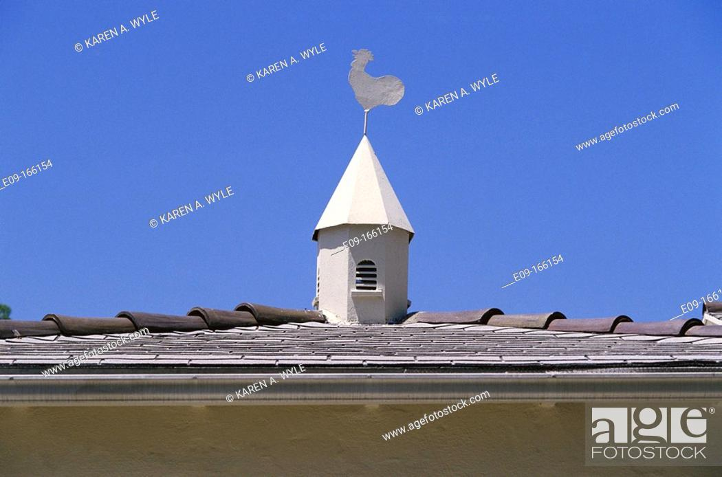 Stock Photo: White rooster weathervane atop small white towerlike feature on tile roof, against blue sky. Los Angeles. California. USA.