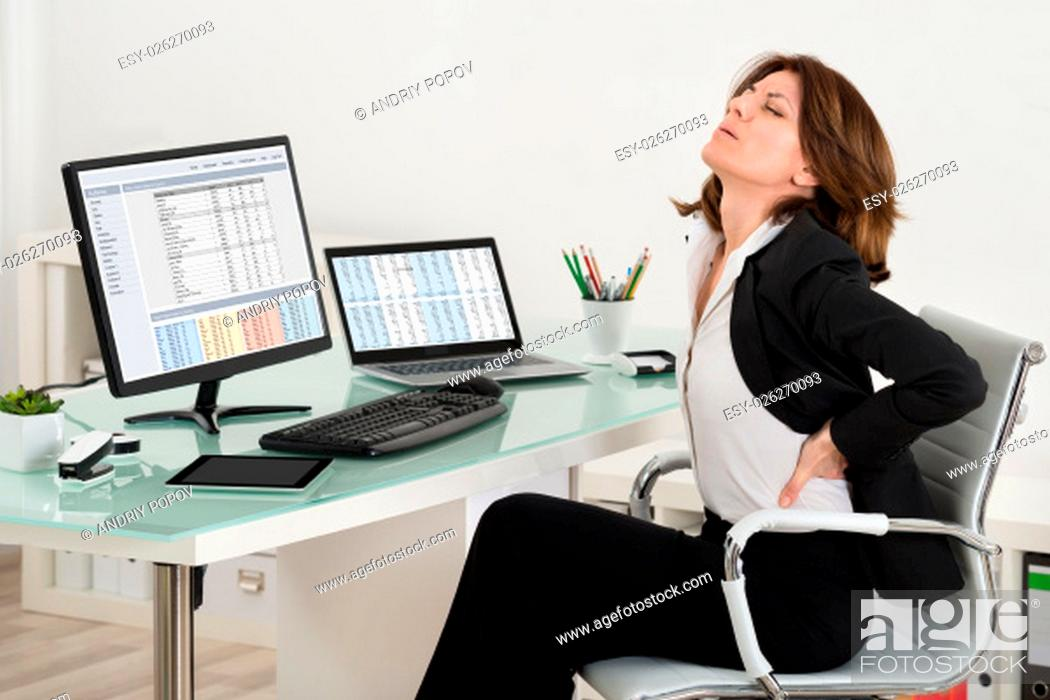 Stock Photo: Businesswoman Suffering From Backache While Working In Office.