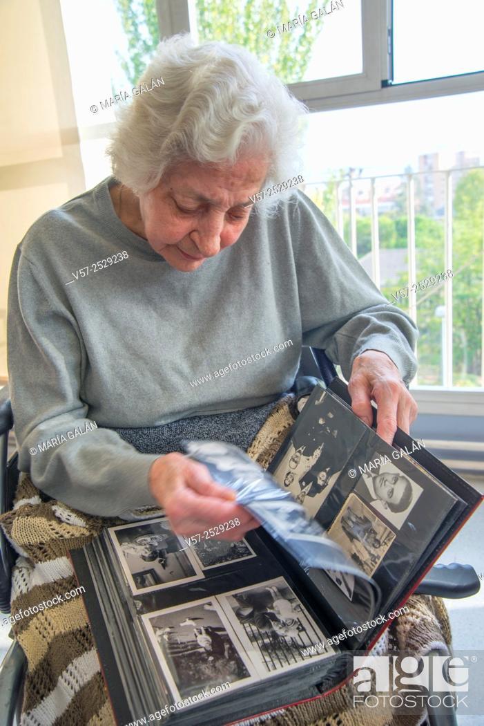 Stock Photo: Old woman leafing through a family photo album in a nursing home.