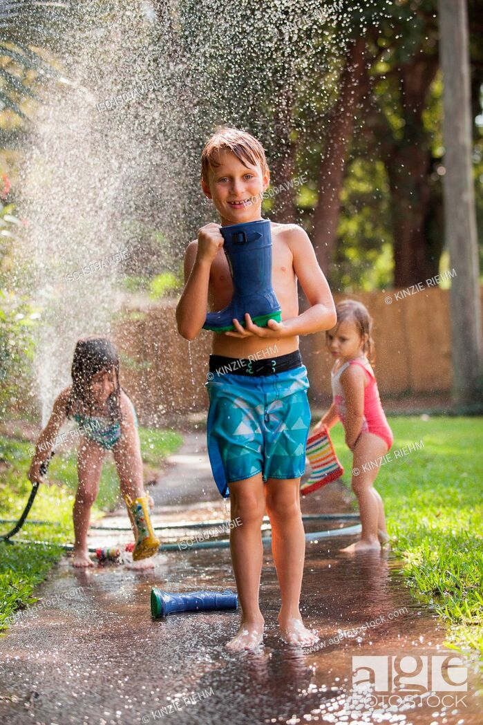 Stock Photo: Boy carrying welly on sidewalk, girls playing with water hose in background.