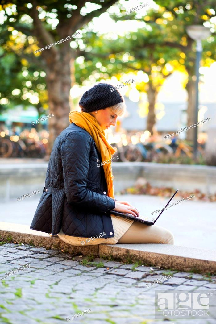 Photo de stock: Side view of woman using laptop while sitting on retaining wall at park.