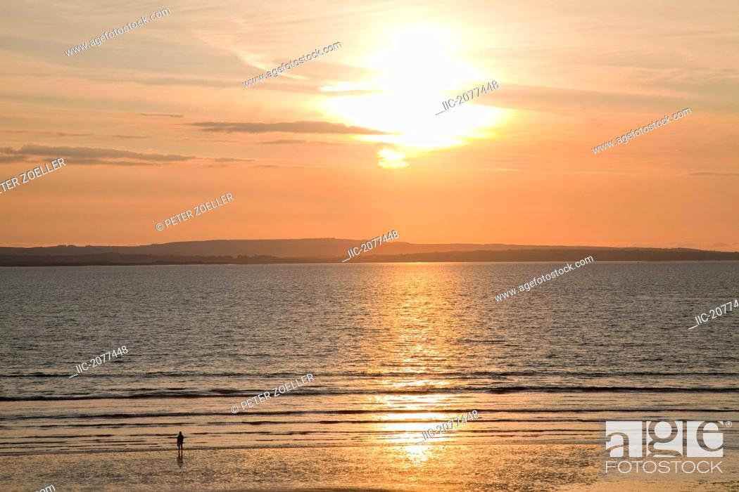 Stock Photo: Silhouette of a person standing on the beach at the water's edge at sunset, inishcrone county sligo ireland.