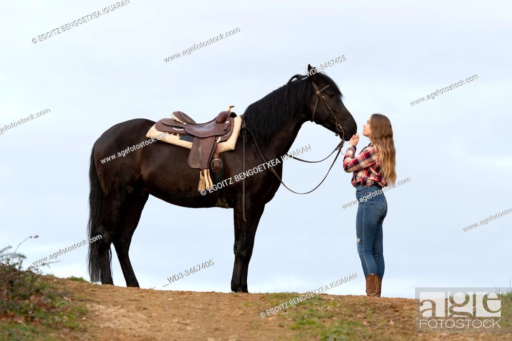 Stock Photo: Side view of a blonde teenager cowgirl in front of her black horse with the saddle.