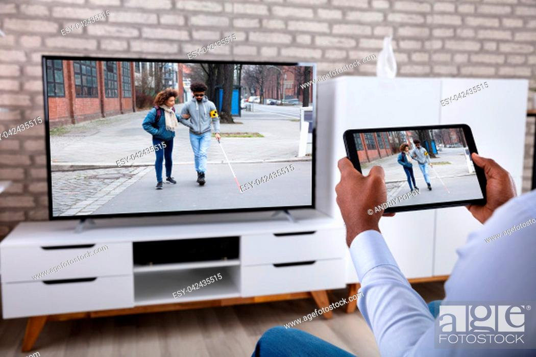 Stock Photo: Man Connecting Television Channel Through Wireless On Digital Tablet At Home.