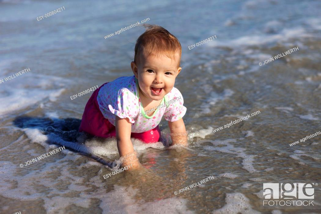 Stock Photo: baby girl playing in water at beach.