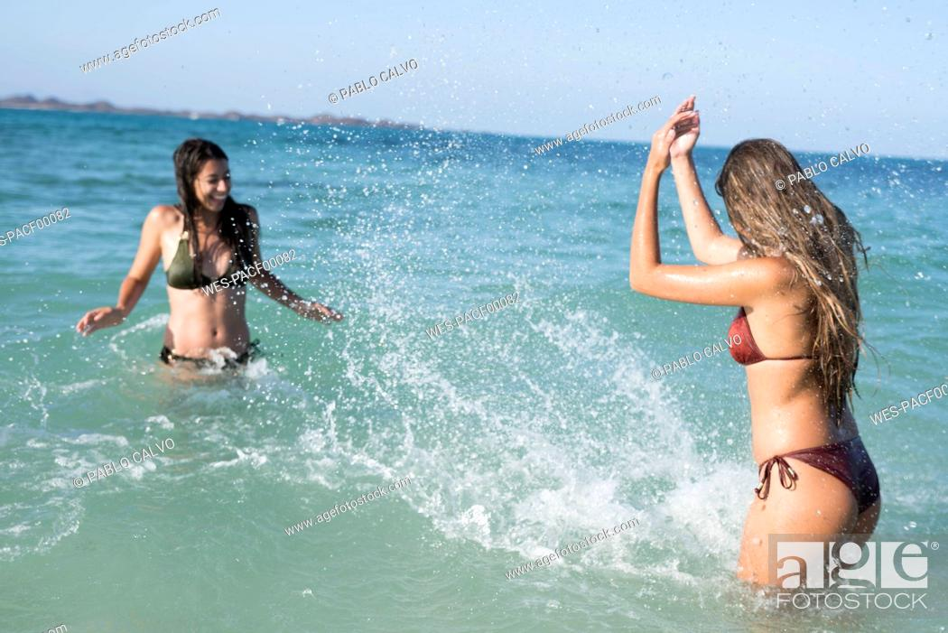 Stock Photo: Happy carefree friends splashing in the sea.