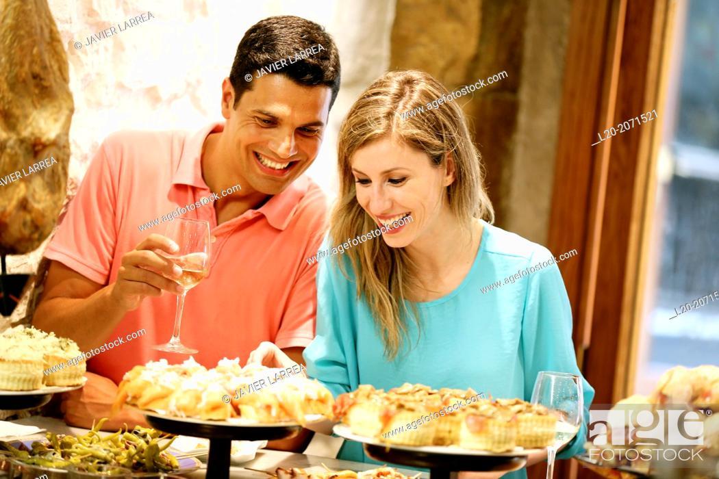 Stock Photo: Couple drinking wine and eating tapas. Pintxos. Bar txondorra. Parte Vieja. Old town. San Sebastian. Donostia. Gipuzkoa. Basque Country. Spain.