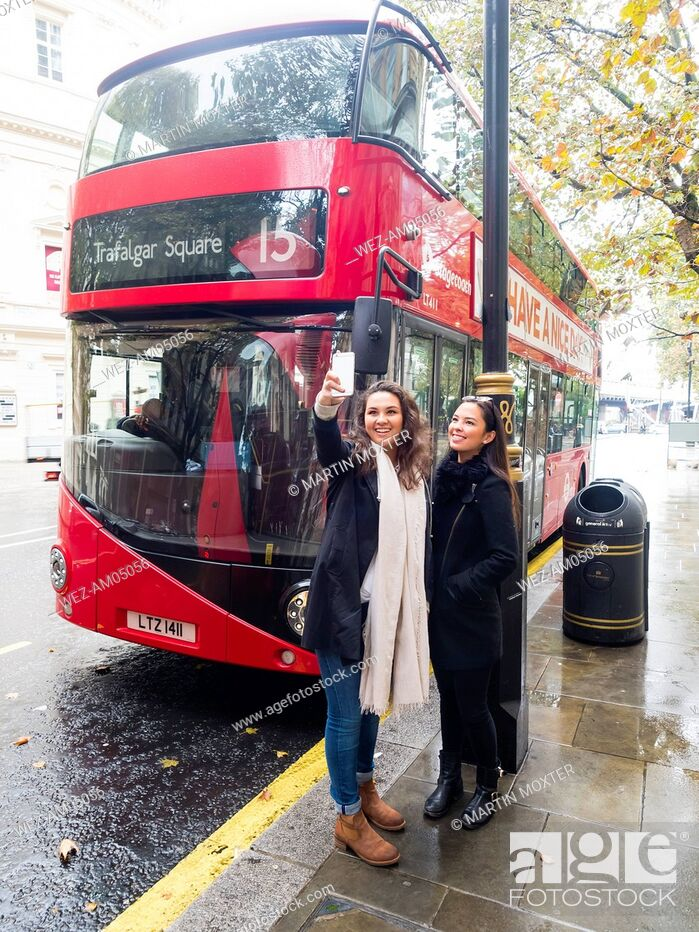 Imagen: UK, London, two happy friends taking selfie with smartphone in front of red double-decker bus.