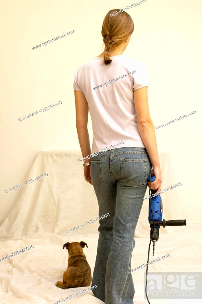 Stock Photo: Rear view of a young woman holding an electric drill machine.