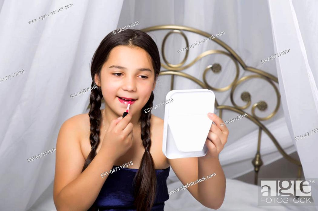 Photo de stock: little girl sitting on a bed looks in the mirror and painting lips like her mom.