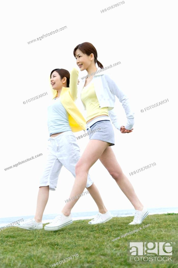 Stock Photo: Young Women walking on lawn, low angle view.