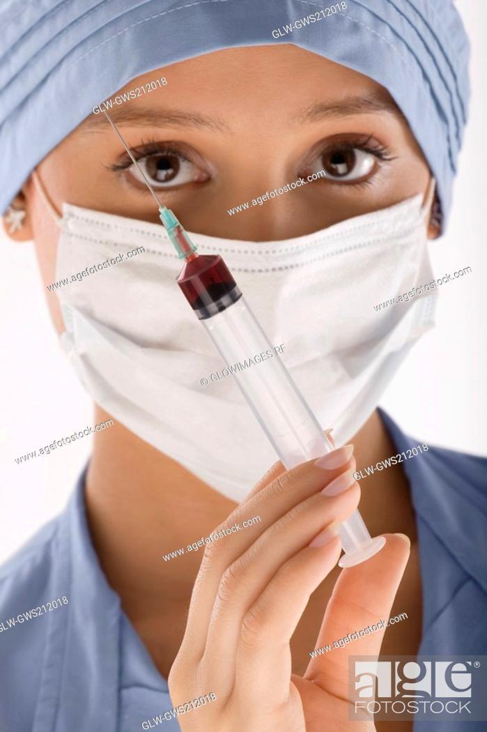 Stock Photo: Portrait of a female surgeon holding a syringe.